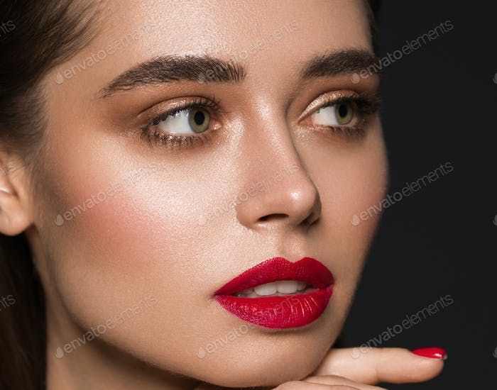 Fashion model woman makeup red lips beauty female black background. Studio shot.