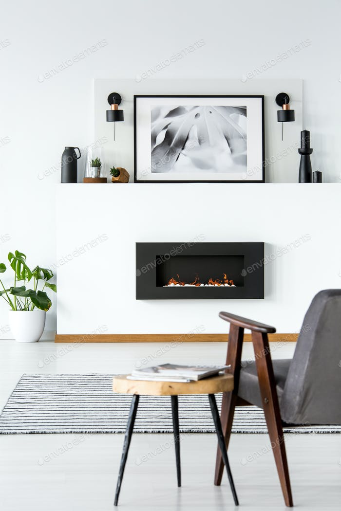 Table next to grey armchair in white loft interior with poster a