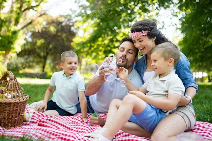 Familie mit Kindern blasen Seifenblasen im freien