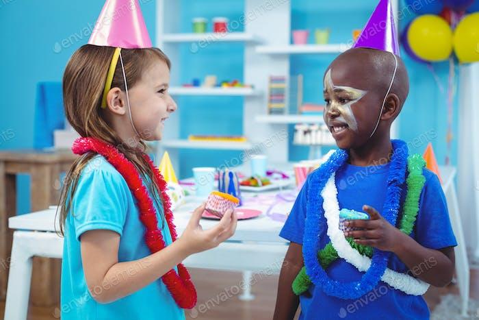 Happy kids enjoying tasty buns at the birthday party