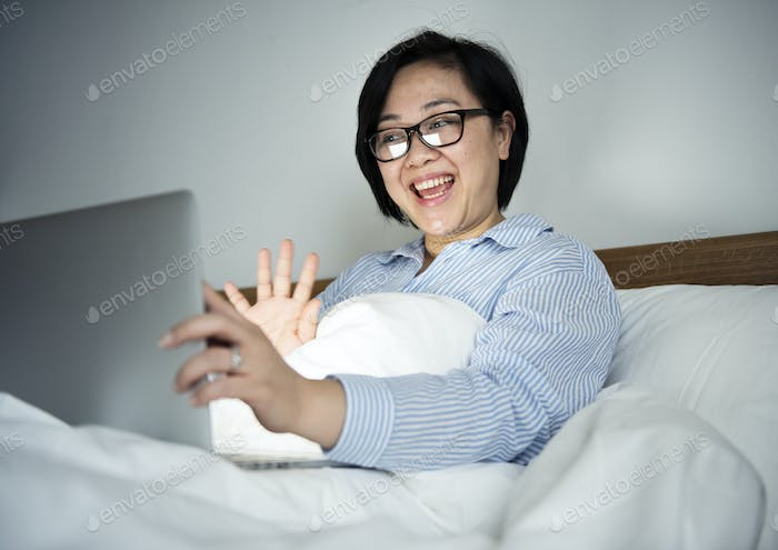 A woman working on a laptop in bed