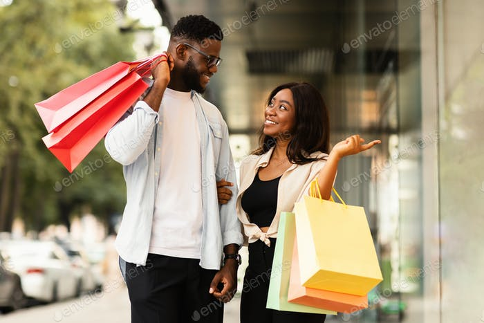 Portrait of black couple walking with shopping bags