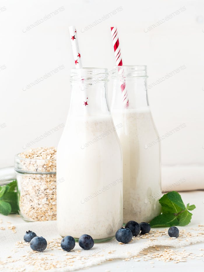 Smoothie with oatmeal,. Oat milk in glass bottle