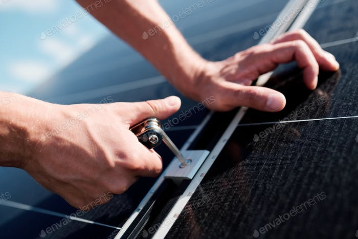Hands of professional technician or engineer installing solar panels