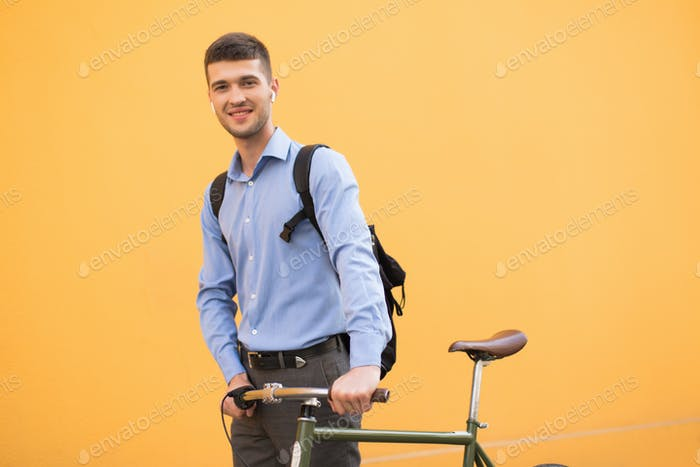 Young attractive man in blue shirt and backpack with wireless ea