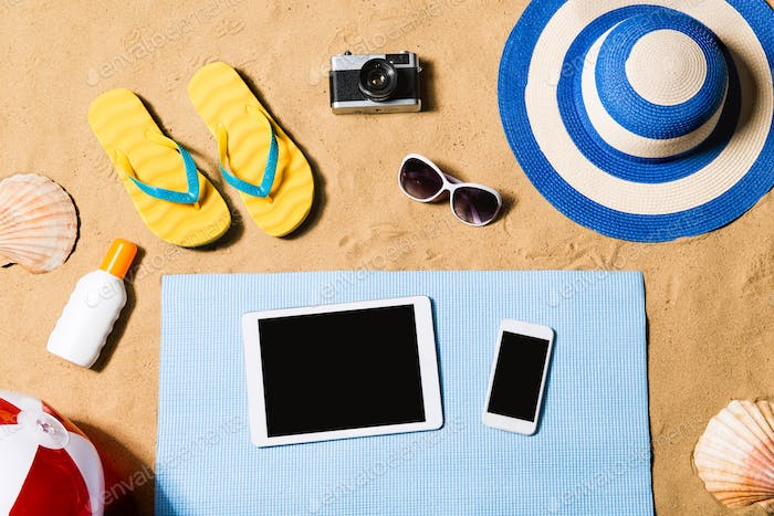 Summer vacation composition. Sandals, hat, tablet and smartphone