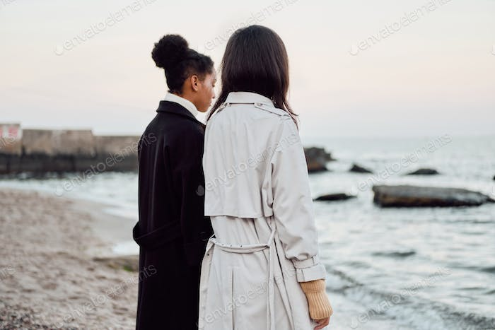 Back view of two casual stylish girls in trench coats dreamily standing by the sea