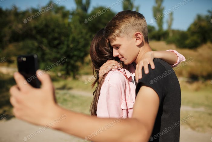 Young beautiful couple standing and embracing each other while making selfie in park