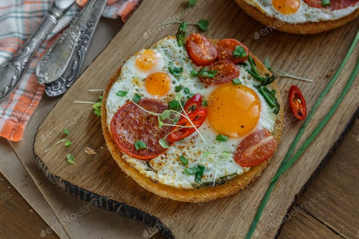 Sunny side fried eggs with tomato and bread on cutting board