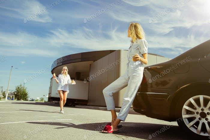 Young lesbian's couple preparing for vacation trip on the car in sunny day