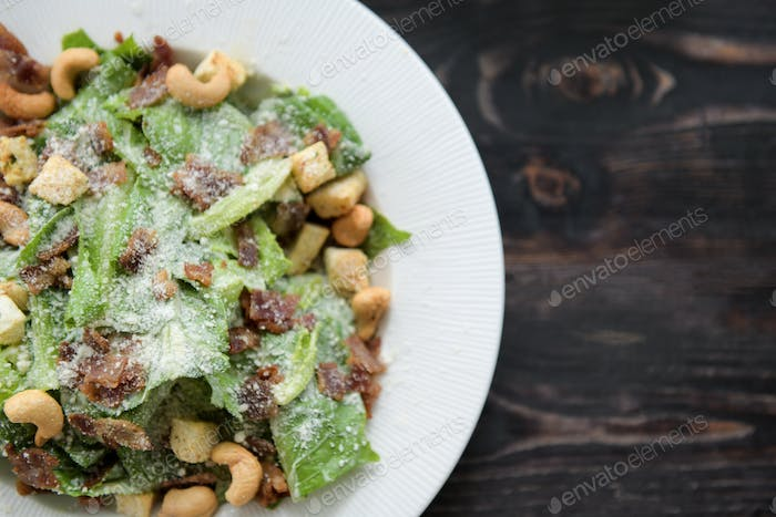 Caesar salad on wooden floor.