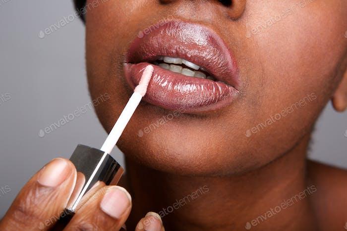 Close up beautiful african american woman applying shiny lip gloss