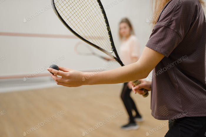 Female players with squash rackets, focus on ball
