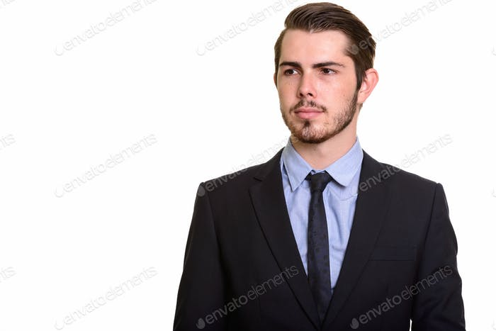 Portrait of young handsome bearded businessman in suit