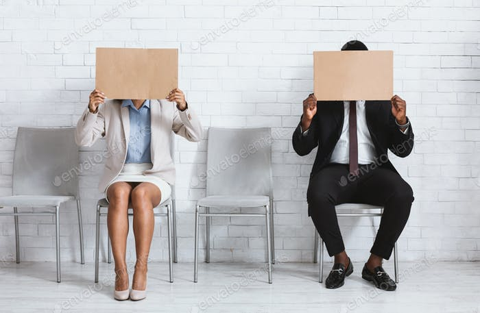 African American job applicants closing their faces with blank signs at company office, space for