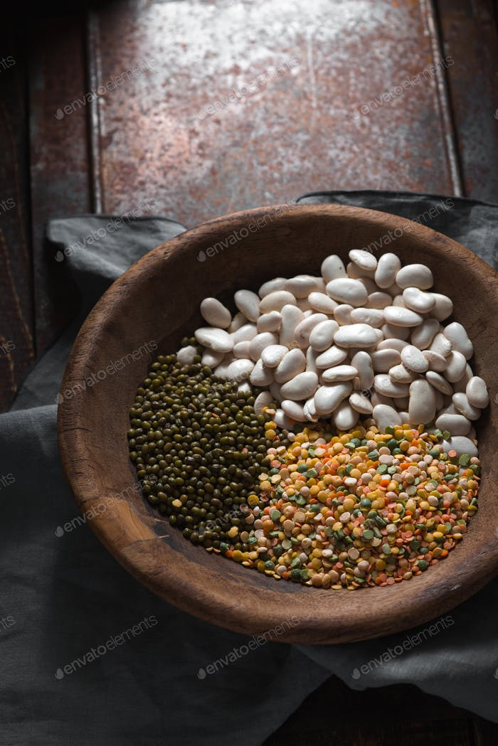 Placer green and white beans in a wooden bowl