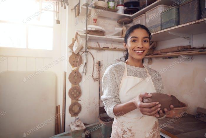 Retrato de la mujer alfarera usando delantal sosteniendo bulto de arcilla en el estudio de cerámica