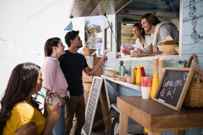 Smiling waiter taking order from couple