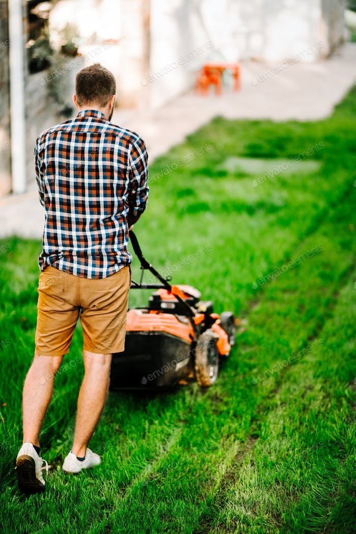 Garden maintenance details - portrait of gardener with grass mower