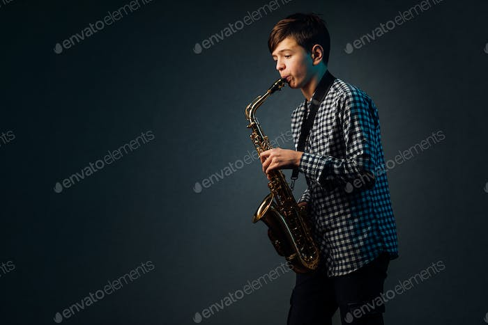 A boy on a dark background with a searchlight plays saxophone