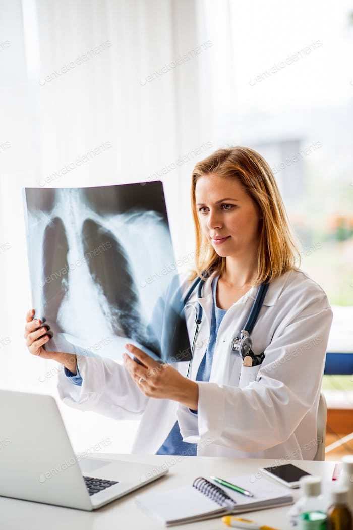Female doctor with x-ray , working at the office desk.