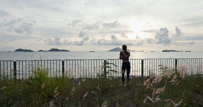 Mujer disfruta de la vista al atardecer en la playa