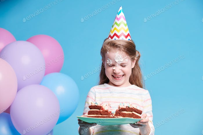 Cute funny girl laughing while holding plate with birthday cake