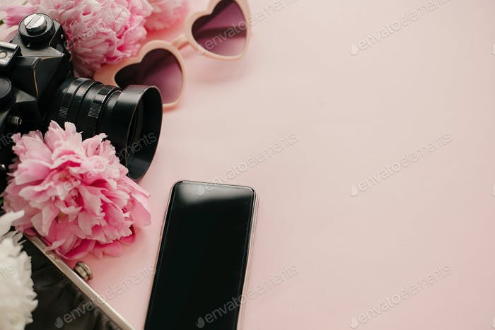 Pink sunglasses, photo camera and vintage purse with pink and white peonies on pastel pink paper
