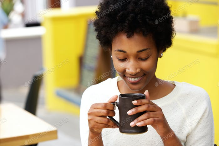 Happy young black woman drinking coffee
