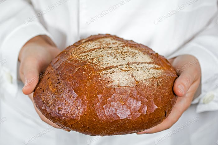 Baker holding fresh bread in the hands of