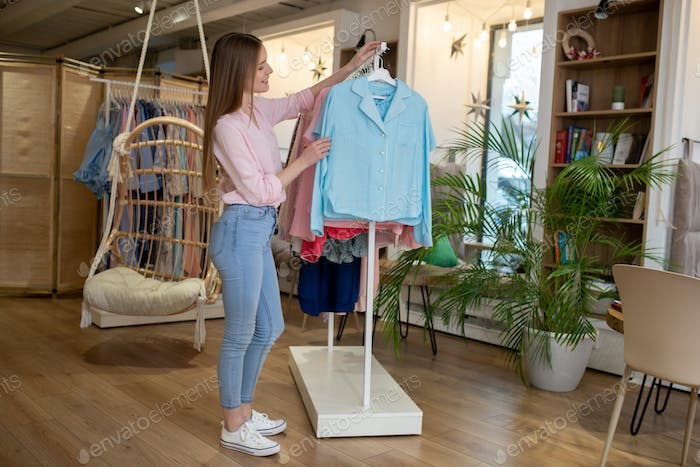 Girl consultant shows a suit hanging on a counter.
