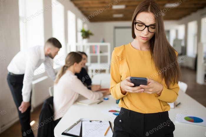 Beautiful business woman in eyeglasses using cellphone in office