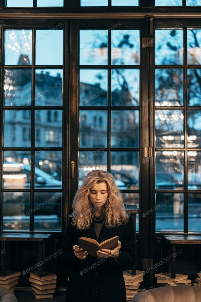 Thumbnail for Woman reading a book on the background of window