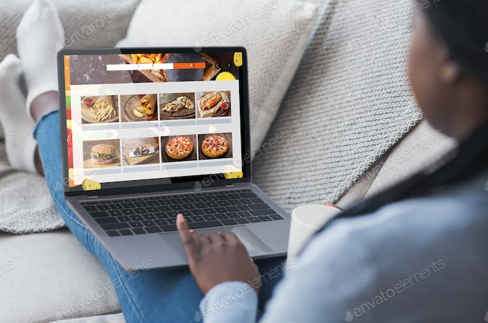 Black Woman Using Laptop Ordering Food Delivery Online Sitting Indoors