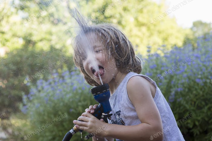 5 year old boy drinking from water hose