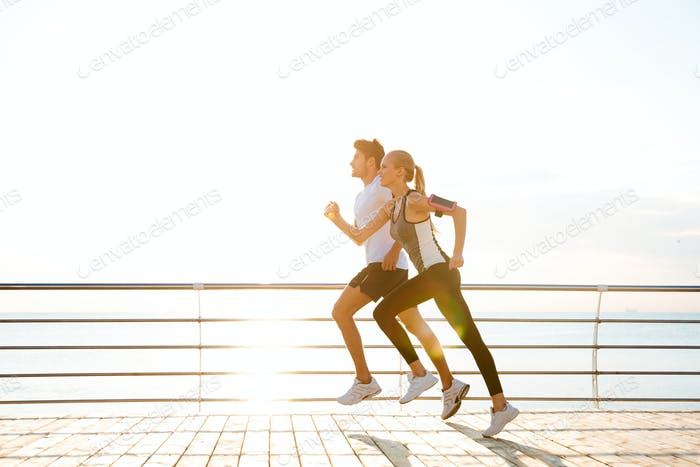 Young couple running over wooden pier