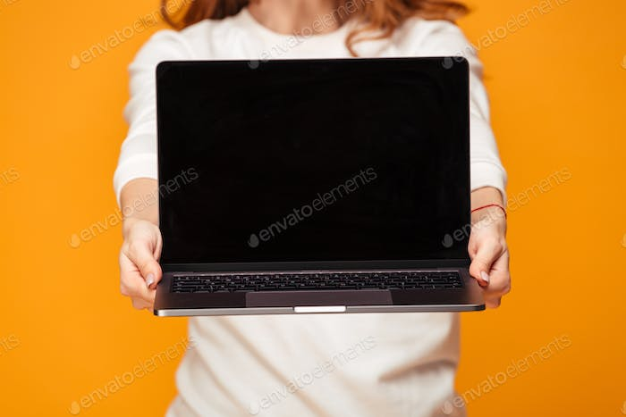 Cropped image of brunette woman showing blank laptop computer screen