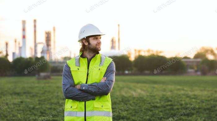 Young engineer standing outdoors by oil refinery, arms crossed