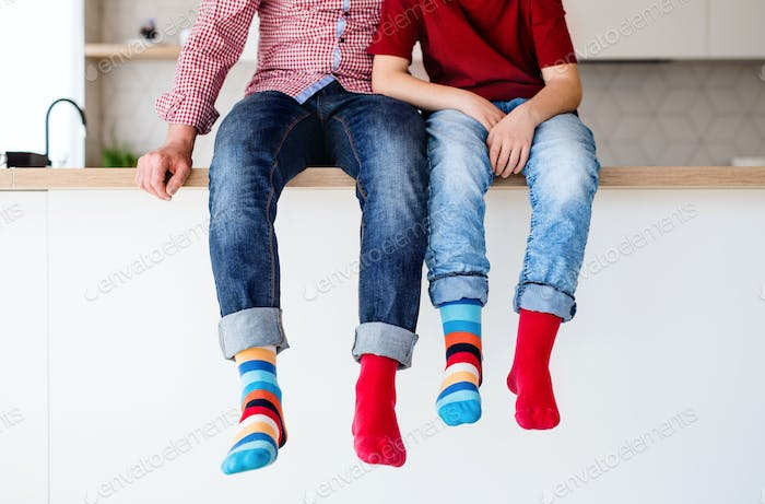 Midsection of father with son with funky socks sitting on kitchen counter indoors