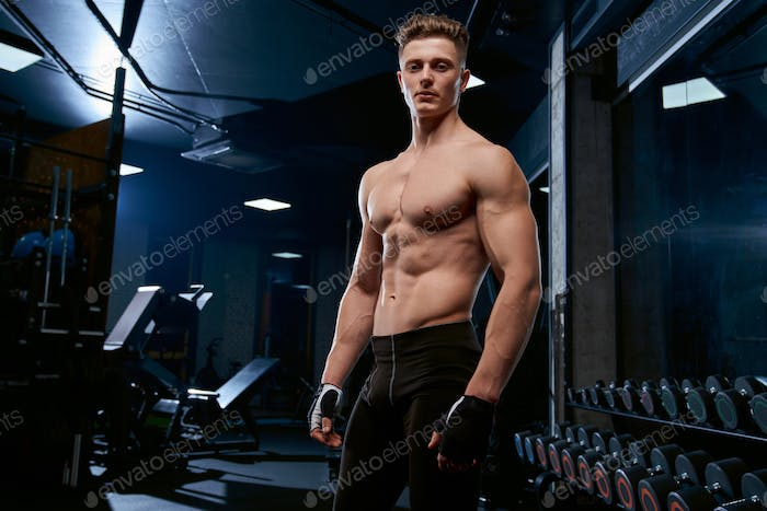 Shirtless sportsman posing in gym