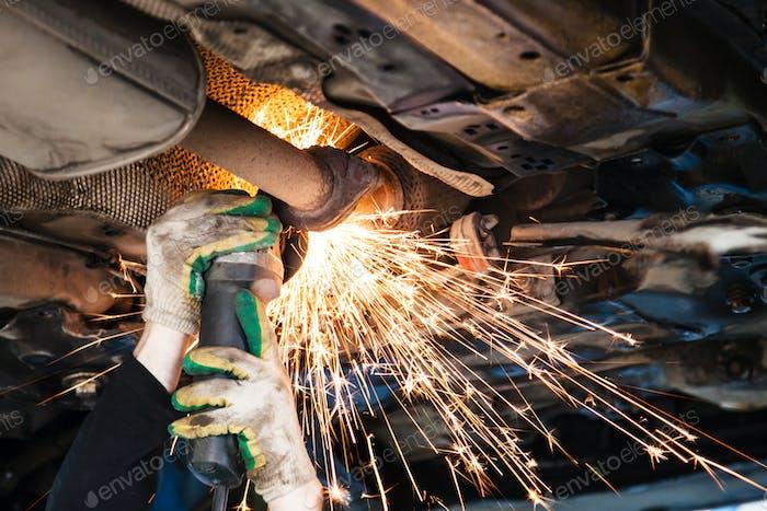 Reparaturer schneidet alten Schalldämpfer auf Auto durch Winkelschleifer
