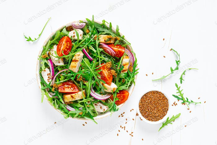 Fresh vegetable salad with grilled chicken fillet, breast, tomato and arugula, top view