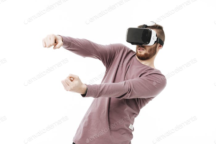 Young man in virtual reality glasses playing car simulator over white background