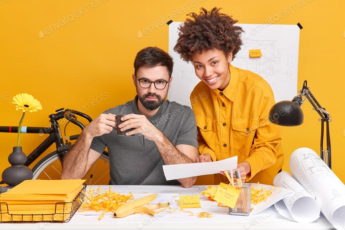 Mixed race woman and man collaborate together discuss future project and try to find best variant fo