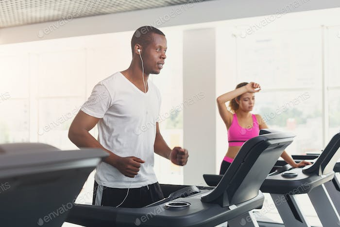 Man and woman, couple in gym on treadmills