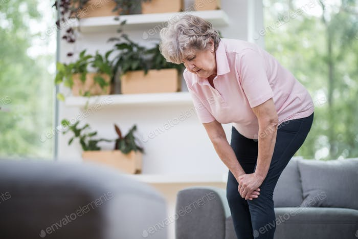 Grey senior lady in pink t-shirt having problem with getting up from the couch