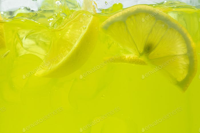 Close up view of the lemon slices in lemonade on background