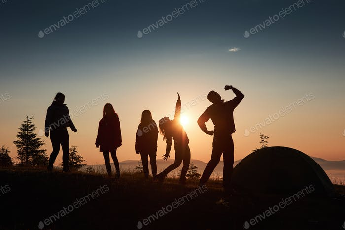 A silhouette of group people have fun at the top of the mountain near the tent during the sunset