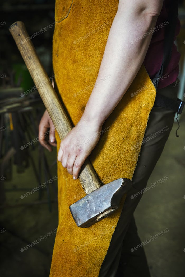A blacksmith in a heatproof apron holding a large hammer.