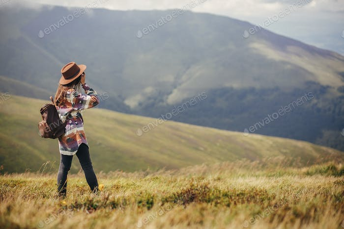 Traveler girl holding hat, with backpack and windy hair, walking in mountains in clouds